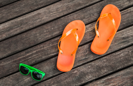 pair of orange flip-flops and green sunglasses on the wooden planks of a jetty photo