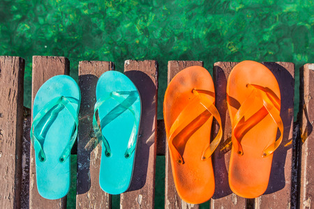 two pair of turquoise green and orange  flip-flops on the wooden planks of a jetty  over the sea photo