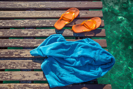 pair of orange flip-flops and a blue towel on the wooden planks of a jetty over the sea photo