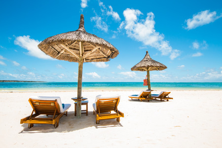 beach umbrella: beautiful tropical beach with green coconut palms straw sunshades and wooden sunbeds in front of a turquoise sea with a blue sky, Mauritius, Africa Stock Photo