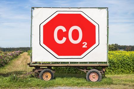 필드의 앞에 트레일러와 농촌 현장. 트레일러에는 CO2라는 문자가 적힌 큰 빨간 정지 신호가 있습니다. 탄소 dioxyde를 줄임으로써 환경 보호 개념 스톡 콘텐츠