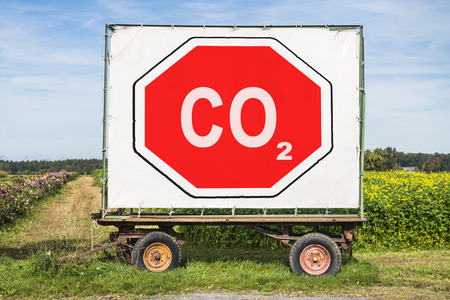 rural scene with a trailer in front of a field. On the trailer is a big red stop sign with the letters CO2. Concept for environment protection by reducing carbon dioxyde