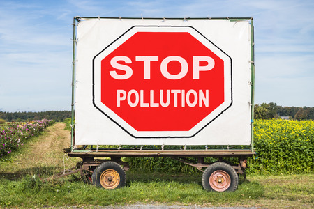 stop pollution: rural scene with a trailer in front of a field. On the trailer is a big red stop sign with the words stop pollution. Concept for environment protection