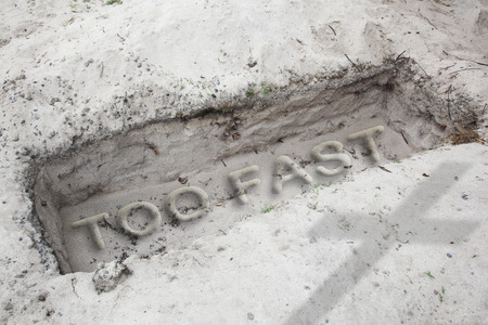 too fast: Open grave in the desert. In  the sand are written the words too fast. Concept for danger caused by driving too fast