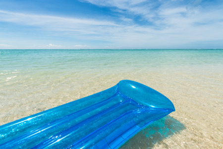 travel background with a blue air mattress floating in a turquoise sea and inviting to relax, Mauritius; Africa