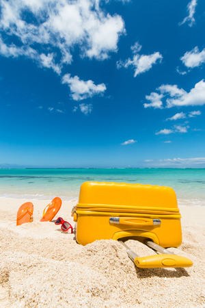 travel background with a yellow trolley, a pair of orange flip-flops and red sunglasses in the sand of a beautiful beach, Le Morne, Maurtius, Africa Banco de Imagens