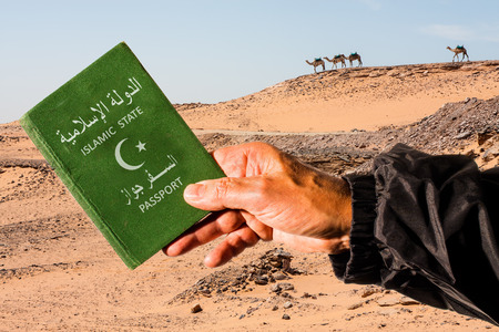 iraq: Sahara desert with camels in the background and a male arm holding a green passport with a white half moon and star. The words islamic state and passport are written in arabic and english language