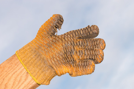 parody: old yellow glove on a wooden plank showing thumb up in the sky. Parody concepts for success