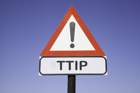 internationally: White road warning triangle with black exclamation point and red frame on a wooden mast in front of a blue sky. A second rectangular sign warns in english about TTIP