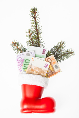 christmas bonus: red and white St Nicholas boat with euro banknotes and a branch of a fir. Business concept for christmas bonus or poison