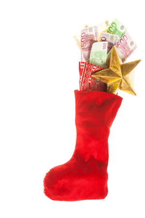 christmas bonus: red and white St Nicholas sock with euro banknotes and a golden star. Business concept for christmas bonus or poison