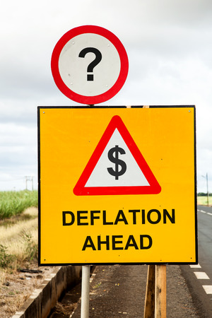 deflation: Yellow traffic sign and a red warning triangle with the message Dollar Deflation ahead beside the road. Business or financial concept asking if deflation threatens. Stock Photo