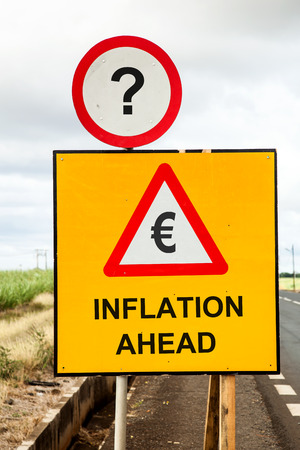 Yellow traffic sign and a red warning triangle with the message Euro Inflation ahead beside the road. Business or financial concept asking if inflation threatens.