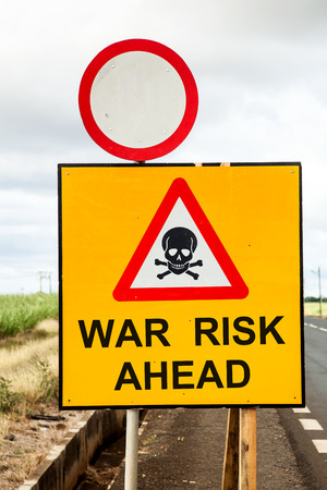 risk ahead: social concept with a yellow traffic sign and a red warning triangle with a skull and the message war risk ahead beside the road Stock Photo