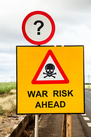 threatens: Yellow traffic sign and a red warning triangle with a skull and the message war risk ahead beside the road. Social concept asking if war threatens.
