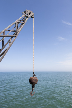 dockside: logistic background with a vintage dockside or ship crane with tow and hook, sea and blue sky in the background, business concept for getting hooked
