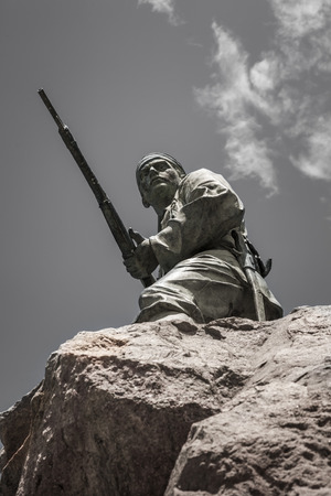 Soldier with gun on the rock of the Marine monument, remembering the German soldiers killed during the Herero rebellion 1904-1905, Swakopmund, Namibia, Africa Stock Photo
