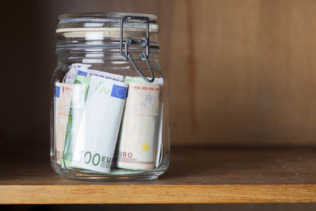 preserving glass with Euro banknotes in a wooden shelf, financial concept for saving money