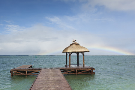 end of rainbow: two egyptian goose on a straw hut at the end of a jetty over the sea and a rainbow under the blue sky, Mauritius, Africa Stock Photo