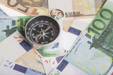 deflation: magnetic compass on euro banknotes. financial concept for the trend of the euro exchange rate,  inflation or deflation