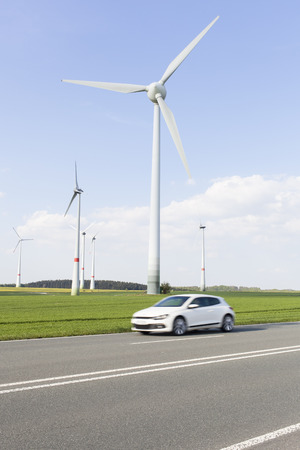 Wind turbines near a country road with a nearly white electric car passing by concept for ecology Green Energy Technology Progress Transportation and Modern Life