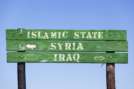 Green wooden signpost with arrows showing the directions to Syria Iraq and the Islamic State. Political Concept Concerning the war in Middle East