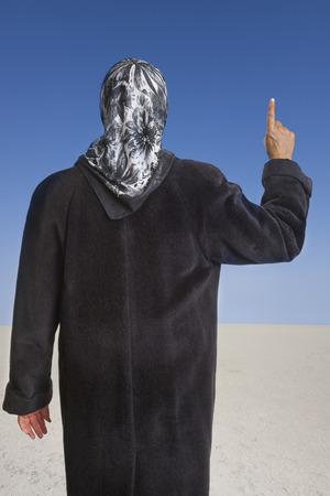 femme musulmane: femme musulmane vêtu d'un manteau noir et foulard levant son index droit dans le désert d'un Etat islamique. concept pour le comportement religieux des musulmans