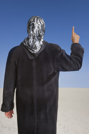 muslim woman dressed with a black coat and headscarf raising her right index finger in the desert of an islamic state. concept for religious behavior of muslim people