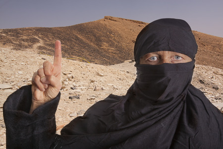 burqa: black dressed and veiled muslim woman raising her right index finger in front of mountains in the desert of of an islamic state. concept for religious behavior of muslim people Stock Photo