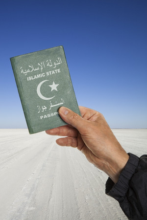 concerning: male hand in the desert holding a passport with the words islamic state in arabic and english language and a white half moon and star. Political concept concerning the war in  Middle East. Stock Photo