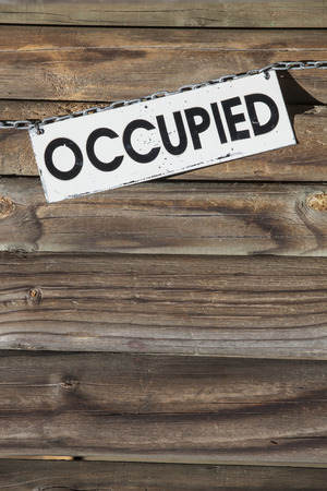 occupied: white metal sign with the word occupied hanging at a chain  in front of a wooden wall. Concept for all things being occupied