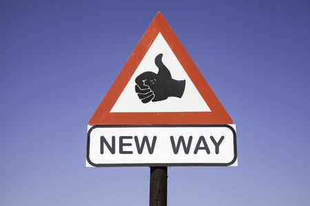 change business: red and white warning triangle traffic sign with a human hand showing thumb up and the words new way, business concept for motivation and success