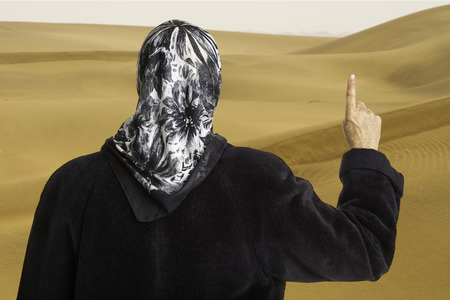 totaled: muslim woman dressed in a black coat and scarf showing the raised pointer finger of her right hand in front of sand dunes of Sahara desert.