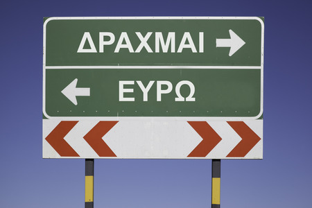 greek currency: Green traffic sign with arrows, showing the decision between the way to Euro or the greek currency Drachma. Financial concept for the greek debt crisis and the word Drachma and Euro in greek letters
