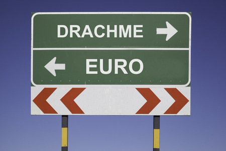 greek currency: Green traffic sign with arrows, showing the decision between the way to Euro or Drachma The Greek currency. Financial concept for the Greek debt crisis