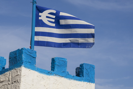 greek currency: Blue and white greek flag with a Euro currency sign on the tower of a castle. Financial concept for the greek Euro crisis