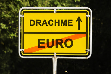 greek currency: yellow european town sign, showing did Greece is leaving the euro and is on the way launching the old currency Drachma. Financial concept for the Greek debt crisis and the German word drachma
