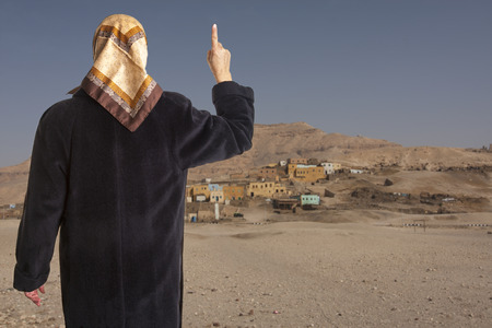 islamic pray: muslim woman dressed in a black coat and scarf showing the raised pointer finger of her right hand in front of an arabic village in the desert.  Stock Photo