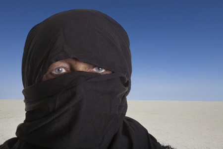 portrait of a black veiled woman in front of a white desert with blue sky.