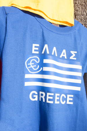 greek currency: Blue and white greek flag with a Euro currency sign on a t-shirt. Financial concept for the greek Euro crisis