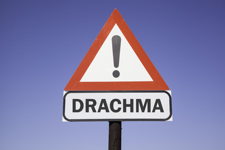 greek currency: red and white warning triangle with the english word Drachma for the greek currency. Financial concept for the greek debt crisis Stock Photo