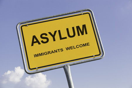 persecution: Yellow european town sign, with the words Asylum and Immigrants welcome. Social concept for immigration from Africa to Europe