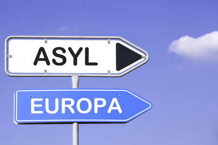 Blue sky behind two white and blue road signs  on a metal mast with arrows to the right side showing the way to Asylum and Europe in german. Social concept for immigration from Africa to Europe