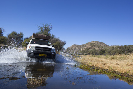 water wheel: white four by four car crossing a river with splashing water, Travel concept for off-road adventure and fun in a south  african landscape Stock Photo