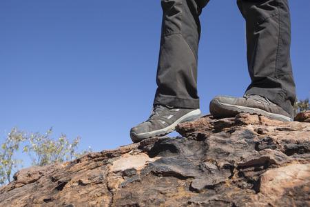 metas: dos piernas con botas grises en la cima de una monta�a. Concepto del recorrido para ir de excursi�n de aventura en la naturaleza y alcanzar una meta Foto de archivo