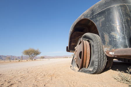 flat tire: old, black car with a flat tire in the desert, concept for  off-road sport or traveling and adventure, Namibia, Africa Stock Photo
