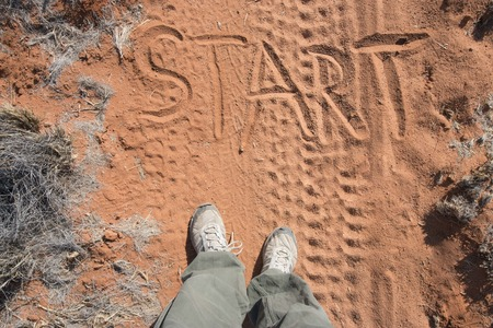 desert sand: the word start written in red desert sand and two human feet before. Motivation concept for beginning a new way, live or job Stock Photo