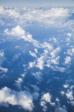 vertical nature background with white cumulus clouds in a deep blue sky