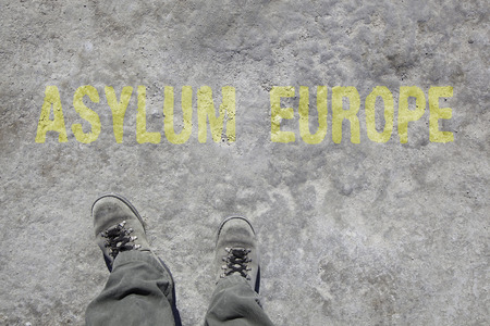 europe: legs with gray boots and the words Asylum and Europe on the ground. Concept for Refugees on their way to Europe.