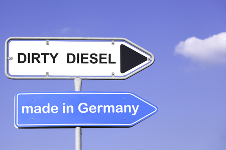 diesel: blue sky behind two road signs  on a metal mast with arrows to the right  side showing the way to dirty Diesel made in Germany. Concept for the  nitric oxide emission crisis of turbo diesel engines
